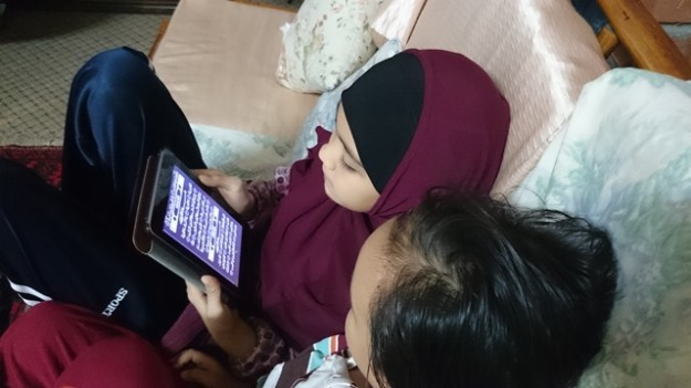 Maryam with the Qur'an on a tablet, with Hasan looking on
